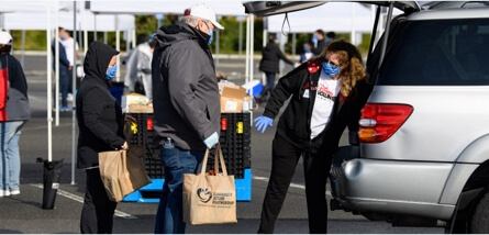 Masked Disney volunteers place donations into car.