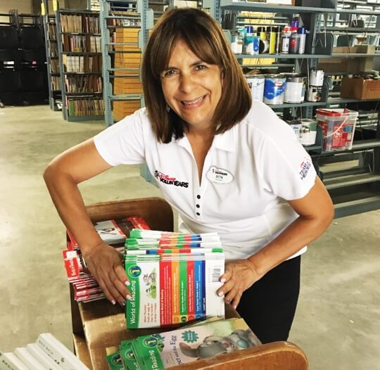 Disney cast member separates and packs book donations.